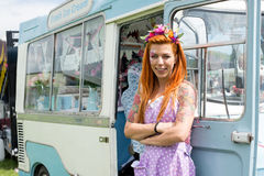Red haired lady standing with vintage ice cream truck. Young red haired lady wearing flower headband standing with vintage ice cream truck. Landscape image with royalty free stock images