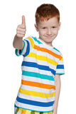 Red-haired little boy holds his thumb up Stock Photo