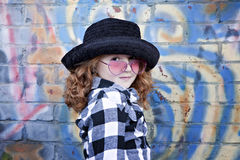 Red haired little girl in front of brick wall Royalty Free Stock Image