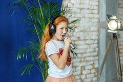 A red-haired little girl sings a song in a microphone. The conce. Pt is childhood, lifestyle, music, singing, listening, hobbies royalty free stock photos