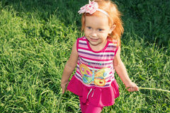 Red-haired little girl walks in the park Stock Photo