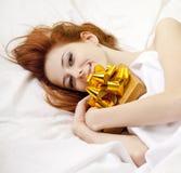 Red-haired Mädchen im Bett mit Geschenk Lizenzfreies Stockbild