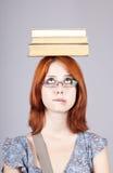 Red-haired Mädchenunterhaltbücher auf ihrem Kopf. stockfoto