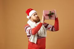 Red-haired man with beard dressed in a red and white sweater with deer, white knitted scarf and a hat of Santa Claus royalty free stock photography