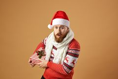 Red-haired man with beard dressed in a red and white sweater with deer, white knitted scarf and a hat of Santa Claus stock images