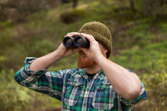 Red haired man looking throw a binocular Stock Image