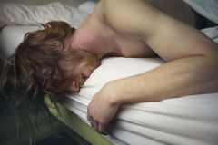 Red-haired man lying in bed looking sick Royalty Free Stock Photos
