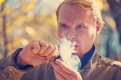 Red-haired man smoking tobacco pipe Stock Photography