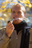 Red-haired man smoking tobacco pipe Stock Images