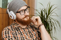 Red-haired man thought while listening to music. Young red-haired hipster thought while listening to music Royalty Free Stock Photos