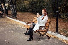 Red-haired middle-aged woman with a smartphone in her hand sits on a bench in the Park and communicates in social. Networks royalty free stock photo