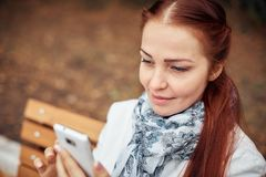 Red-haired middle-aged woman with a smartphone in her hand sits on a bench in the Park and communicates in social. Networks stock photo