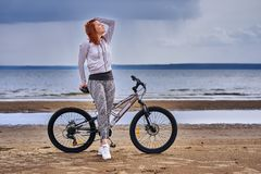 Red-haired middle-aged woman in sportswear on a bike walk on the sandy shore of a large river. Cloudy summer day royalty free stock photos