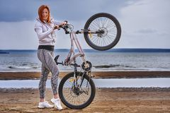 Red-haired middle-aged woman in sportswear on a bike walk on the sandy shore of a large river. Cloudy summer day stock photos