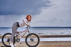 Red-haired middle-aged woman in sportswear on a bike walk on the sandy shore of a large river. Cloudy summer day stock images
