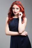 Red-haired model posing in evening dress and in diadem Stock Photos