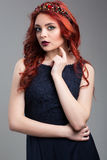 Red-haired model posing in evening dress and in diadem Stock Image