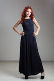 Red-haired model posing in evening dress and in diadem Royalty Free Stock Photography