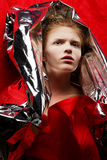 Red-haired model in red with silver cape. Arty portrait of a fashionable red-haired model in red with silver foil cape over red curtain background. Studio shot stock photography