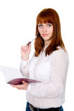 Red-haired pensive female student with a notebook and pen. Royalty Free Stock Photos