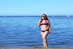 Red-haired plus size woman resting on coast Royalty Free Stock Photos