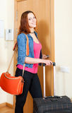 Red haired positive woman comes back home from vacation with bag Stock Photography
