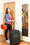 Red-haired positive woman in jeans with luggage leaving the home Stock Photography