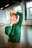 Red-haired professional choreographer with hair bun feeling harmonic. Harmony. Red-haired professional choreographer with hair bun feeling harmonic while getting royalty free stock image