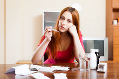 Red-haired sad girl with thermometer in living room Stock Photos