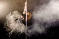 Red haired sexy pole dance girl exercises and poses on the pylon in the smoke. On the black background Stock Image