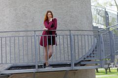 Red-haired slender girl posing standing at the railing against the gray walls stock photo