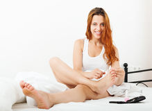 Red-haired smiling girl cares for toenails Royalty Free Stock Photos