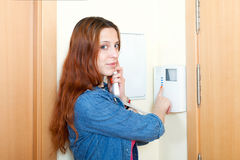 Red-haired smiling girl talking on the house videophone Stock Photography