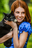 Red-haired smiling young woman with black cat royalty free stock photos