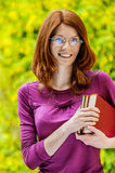 Red-haired smiling young woman with books Royalty Free Stock Photo