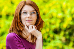 Red-haired smiling young woman with glasses reflects Royalty Free Stock Image