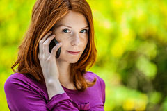 Red-haired smiling young woman talking on phone Stock Image