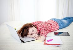Red haired student alseep on laptop while studing Stock Photo