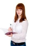 Red-haired student with pen and notebook. Royalty Free Stock Image