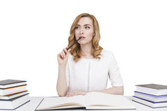 Red haired student at a table with books, isolated Royalty Free Stock Image