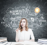Red haired student at a table, business plan Stock Images