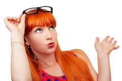 Red-haired surprised girl. Pin-up 50s style red-haired surprised girl in glasses on white background royalty free stock image