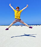 Red-haired teen boy jumping at the beach in Miami Royalty Free Stock Image