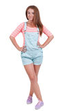 Red-haired teen girl in shorts. Isolated on white background. playful girl in funny pose standing and smiling Royalty Free Stock Photos