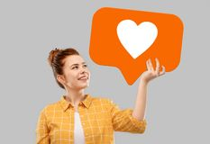 Red haired teenage girl holding heart icon. Social media marketing, internet and people concept - smiling red haired teenage girl in checkered shirt holding royalty free stock photos