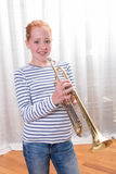 Red haired teenage girl playing the trumpet Royalty Free Stock Image