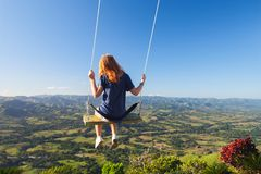 Red haired teenage girl on a swing. Red haired teenage girl swinging on a swing. Montana Redonda. Dominican Republic Royalty Free Stock Photography