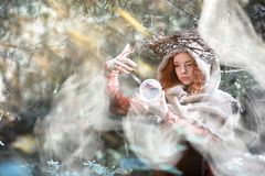 Red-haired witch in a dense forest Stock Image