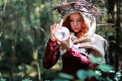 The red-haired witch holds a ritual with a crystal ball Stock Images