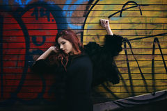 Red haired woman against wall painting Stock Photo